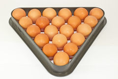 Chicken eggs in the billiard triangle. Fresh chicken beige eggs closeup in the billiard triangle on a white background Royalty Free Stock Images