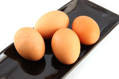 Chicken eggs on black dish. Royalty Free Stock Photography
