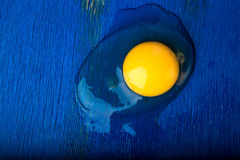 Chicken eggs on blue wooden background. Top view. Broken egg. Royalty Free Stock Images