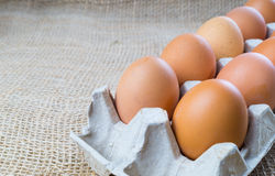 Chicken eggs in box. Brown eggs on sackcloth background with copy space royalty free stock photos