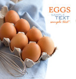 Chicken eggs in the box and whisk Royalty Free Stock Images