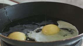 3 chicken eggs are broken into a frying pan slowmotion. Cooking stock video