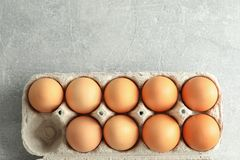 Chicken eggs in carton box on gray background stock photos