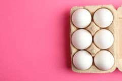 Chicken eggs in carton box on pink background stock photo