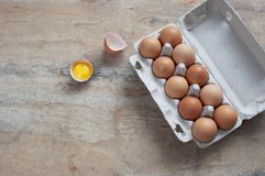 Chicken eggs in carton on wooden table. Eggs Yolk Cooking Top View. Food background royalty free stock images