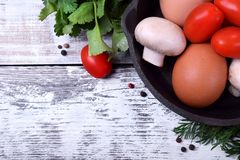 Chicken eggs, champignons and cherry tomatoes in a cast iron pan against the white wooden background stock image