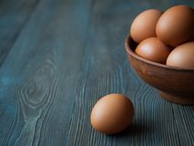 Chicken eggs in a clay pot on dark wooden background. Background with eggs still life eggs in a bowl, one egg rests on a wooden table Stock Photography