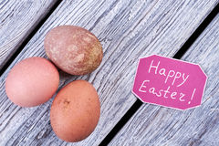 Chicken eggs and congratulatory card. Items on wooden background. Wishes for happy Easter Royalty Free Stock Photography