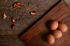 Chicken eggs on cutting board rustic wooden background Stock Image