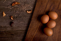 Chicken eggs on cutting board rustic wooden background Royalty Free Stock Images