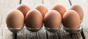 Chicken eggs in an egg box on wooden table stock image