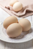 Chicken eggs. Fresh chicken eggs on a white plate on a wooden background stock image