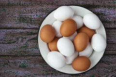 Chicken eggs in a glass and a metall dish on the purple boards Stock Images