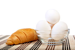 Chicken eggs in a glass vase on a mat and a croissant Royalty Free Stock Photo