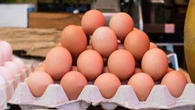 Chicken Eggs Stack on sale in their carton box. Brown color royalty free stock image