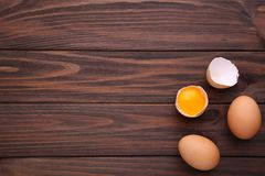 Chicken eggs and half with yolk on a brown background. Eggs on a brown wooden table royalty free stock image