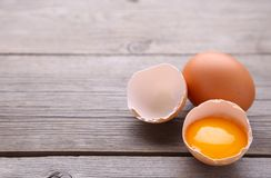 Chicken eggs and half with yolk on a grey background. Eggs on a grey wooden table stock photos