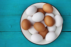 Chicken eggs in a metall dish on the blue boards Royalty Free Stock Image