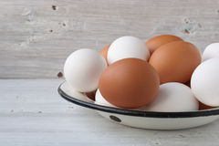Chicken eggs in a metall dish on the white boards Royalty Free Stock Images