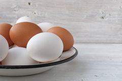 Chicken eggs in a metall dish on the white boards Stock Photography