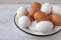 Chicken eggs in a metall dish on the white boards Stock Photo