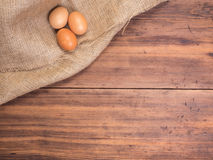 Chicken eggs on old rural wooden table boards and burlap vintage background, photo top view. Hessian texture with eggs stock image