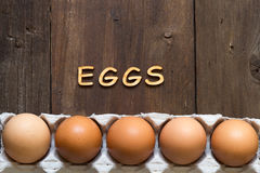 Chicken eggs in the package and the word EGGS Royalty Free Stock Photos