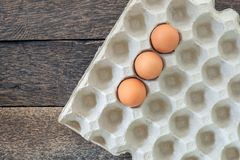 Chicken eggs in paper tray on old wooden background. royalty free stock images