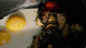 Chicken eggs with potatoes and vegetables roasting in a pan.  stock footage