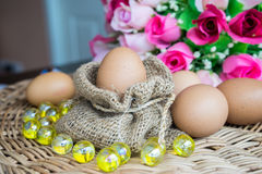Chicken eggs in sackcloth and rose lay down on basketwork Royalty Free Stock Photos