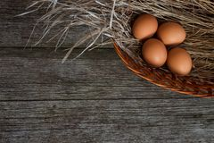 Chicken eggs in straw basket on rustic wooden background Stock Photo