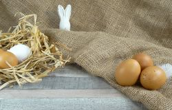 Chicken eggs in straw nest witheaster bunny at burlap over wooden background royalty free stock photo