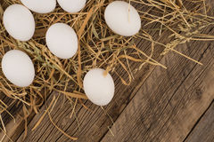 Chicken  eggs in the straw and wooden table. Stock Photography