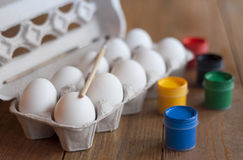 Chicken eggs in a tray, and colorful paint. A dozen white chicken eggs, paint and brush. They lie on a wooden table. Prepared for coloring the holiday of Easter Royalty Free Stock Image