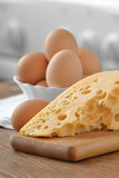 Chicken eggs in white dish with cheese on a wooden Royalty Free Stock Images
