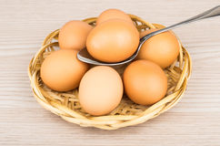 Chicken eggs on wicker basket and egg in spoon Stock Photo
