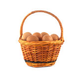 Chicken eggs in wicker basket isolated Stock Image