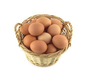 Chicken eggs in wicker basket isolated on white closeup. Chicken eggs in small brown handmade wicker basket isolated on white closeup Stock Photo