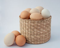 Chicken eggs in a wicker basket on a white background. Three eggs lie beside Stock Photos