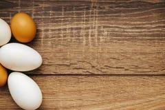 Chicken eggs on wooden background stock photos
