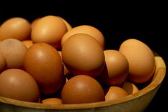 Chicken eggs in wooden basket on black background Stock Photo