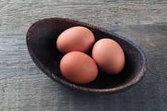 Chicken eggs in a wooden bowl on the table. / Royalty Free Stock Image