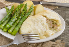 Chicken en Croute. Chicken breast fillet with cheese, bacon and leeks in a creamy sauce wrapped in puff pastry. Served with new potatoes and asparagus tips Royalty Free Stock Photo
