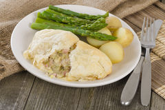 Chicken en Croute. Chicken breast fillet with cheese, bacon and leeks in a creamy sauce wrapped in puff pastry. Served with new potatoes and asparagus tips Stock Image