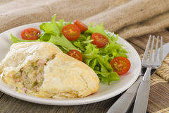 Chicken en Croute. Chicken breast fillet with cheese, bacon and leeks in a creamy sauce wrapped in puff pastry. Served with salad Stock Image