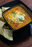 Chicken Enchilada Soup. A bowl of chicken enchilada soup with white corn tortillas on the side Royalty Free Stock Image