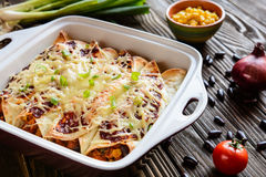 Chicken enchiladas with spicy tomato sauce, corn, beans and cheese Stock Photo