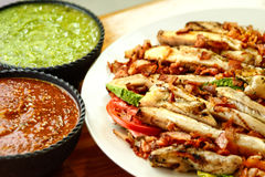 Chicken fajitas with sauces. Chicken fajitas on a white plate with sauces Stock Images