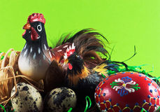 Chicken family with painted eggs. Easter decoration on green background Stock Image