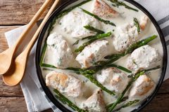 Chicken fillet with asparagus in a creamy sauce close-up on a pl. Ate on a table. Horizontal top view from above Stock Photography